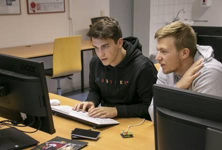 Zwei Elektrotechnik-Studenten lösen eine Aufgabe am Computer