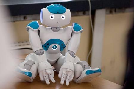 Der humanoide Roboter NAO sitzt auf einem Tisch