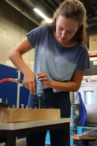 Mädchen dreht Schrauben in ein Holzbrett. Sie benutzt dazu einen Akkuschrauber, der mit Druckluft betrieben wird.