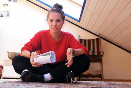 Studentin zeigt eine Geschicklichkeitsübung mit einem Plastikbecher