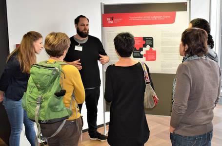 Eine Gruppe diskutiert vor einem Poster zum wissenschaftlichen Arbeiten