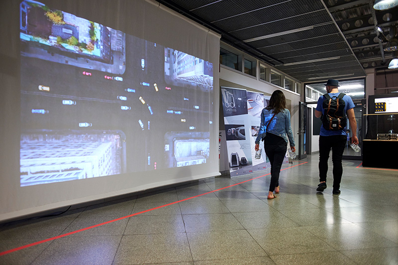 Two students walking past a screen that is being projected on. The projection shows an aerial view of an urban intersection