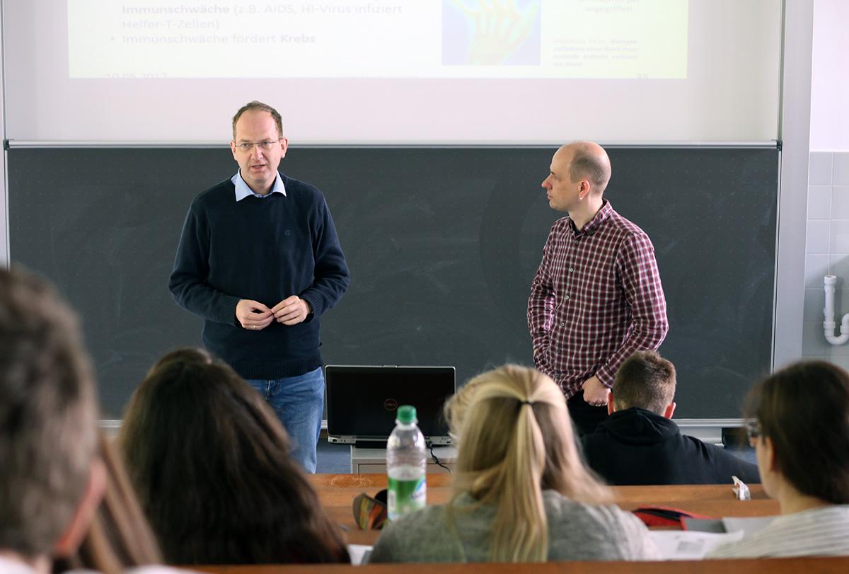 Prof. Noll und Dr. Schmalenberger im Hörsaal mit Studierenden der Bioanalytik.