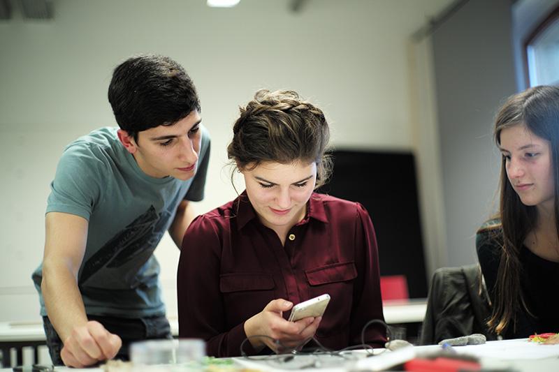 IP-Student Raphael Paschalidis zeigt zwei Schülerinnen, wie man Fotoabzüge künstlerisch gestalten kann