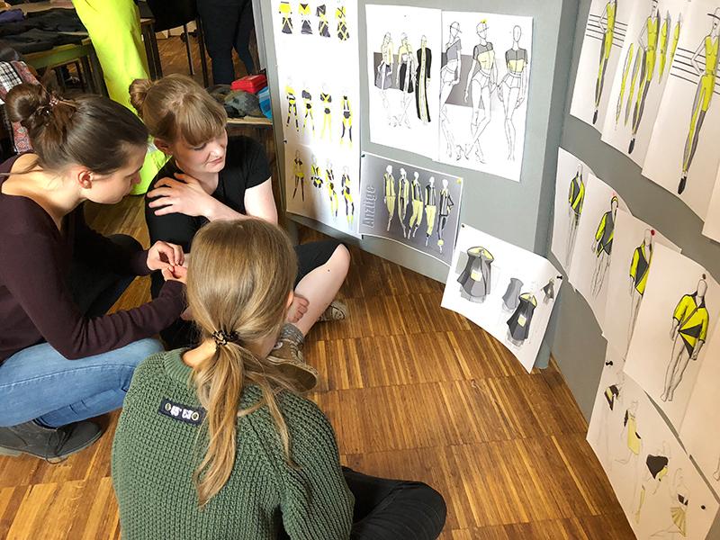 Drei Studentinnen sitzen vor ihren Skizzen der Kleidungsstücke