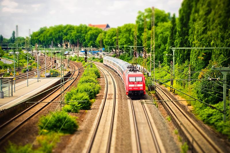 Ein Zug fährt durch einen Bahnhof mit grüner Landschaft
