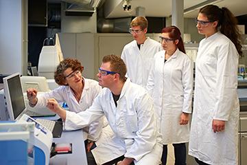 Studierende mit weißen Kitteln im Labor
