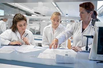 Schülerinnen mit Labormitarbeiterin im Labor.