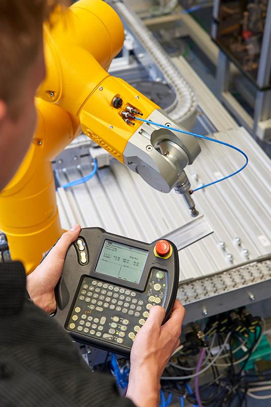 Ein Student bedient einen Industrieroboter.