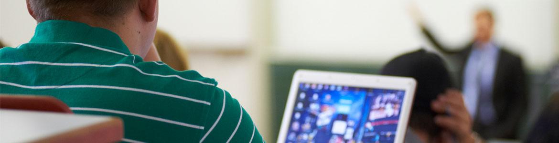 Ein Student mit Laptop im Hörsaal