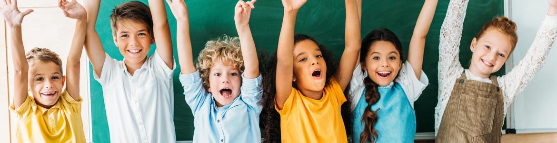 Sechs Kinder stehen mit hochgestreckten Armen vor einer Tafel und jubeln.